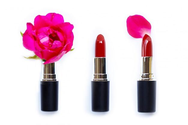 Lippenstifte mit rosafarbener blume auf weißem hintergrund. Premium Fotos