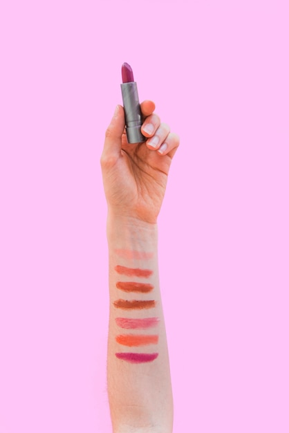 Lippenstiftmuster auf der frauenhand, die lippenstift über rosa hintergrund hält Kostenlose Fotos