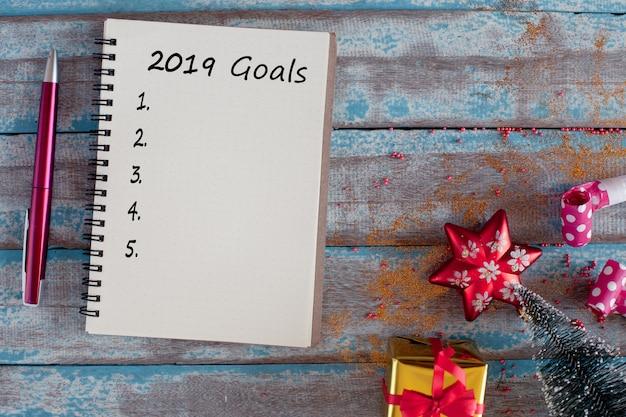 Liste mit 2019 zielen mit notizbuch und stift auf rustikalem blauem holztisch Premium Fotos