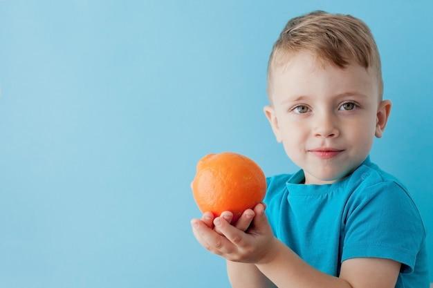 Little boy, das eine orange in seinen händen auf blau hält Premium Fotos