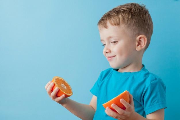 Little boy, das eine orange in seinen händen auf blauem hintergrund, diät und übung für konzept der guten gesundheit hält Premium Fotos