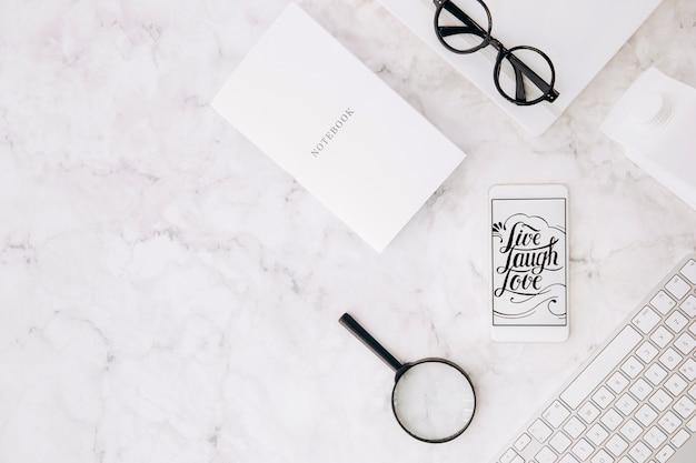 Live lachen liebesbotschaft auf dem mobilen bildschirm; notizbuch; lupe; brille; milchkarton und tastatur auf strukturiertem marmorhintergrund Kostenlose Fotos