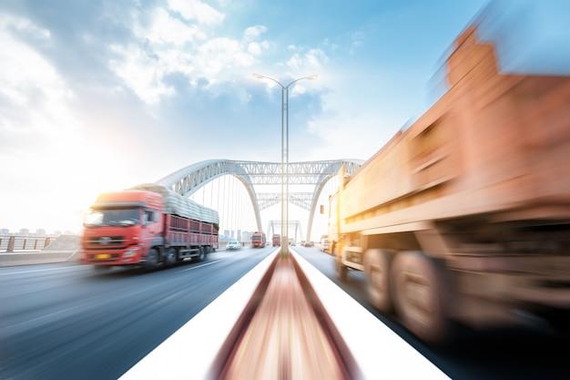 Lkw, der durch eine brücke bei sonnenuntergang, bewegungsunschärfe beschleunigt. Premium Fotos