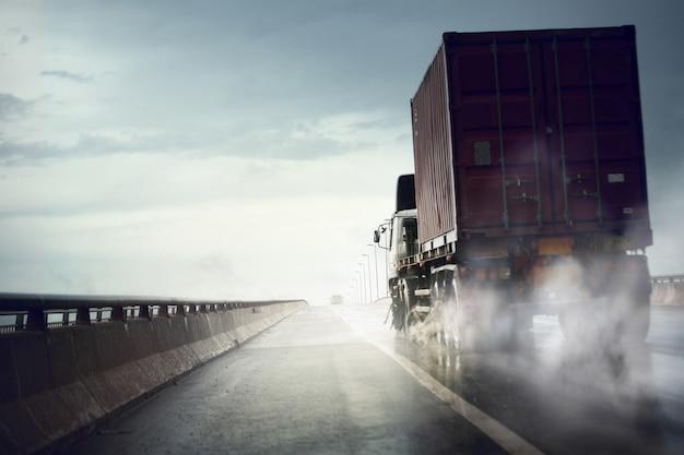 Lkw fährt schnell auf nasser straße nach starkem regen, schlechtem wetter cond Premium Fotos