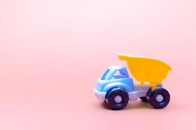 Lkw-spielzeugmodellauto auf rosa hintergrund, raum für text Premium Fotos