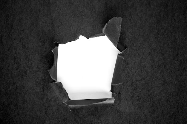 Loch im schwarzen papier mit zerrissenen seiten Premium Fotos