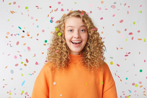 Lockige blondine im orangefarbenen pullover genießt den moment des lebens unter konfetti-regen Kostenlose Fotos