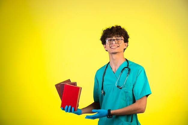 Lockiger junge in medizinischer uniform und handmasken, die seine bücher demonstrieren Kostenlose Fotos