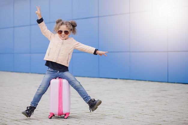 Lockiges lächelndes mädchen der kleinen mode in der sonnenbrille, die auf dem koffer sitzt und frieden durch finger zeigt. Premium Fotos