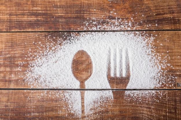 Löffel und gabel formen auf zuckerpulver über dem hölzernen schreibtisch Kostenlose Fotos