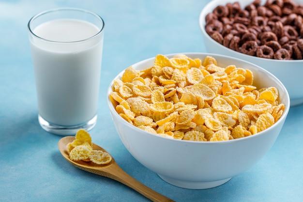 Löffel und schüssel mit schokoladenringen, gelb bereiften corn flakes und einem glas milch zum trockenes, getreidefrühstück Premium Fotos