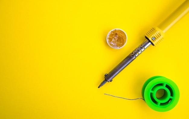 Lötkolben, zinn, kolophonium auf einem gelben tisch. lötkolben in männlichen händen. reparatur von elektrischen geräten, funktechnik. lötdrähte, kontakte. Premium Fotos