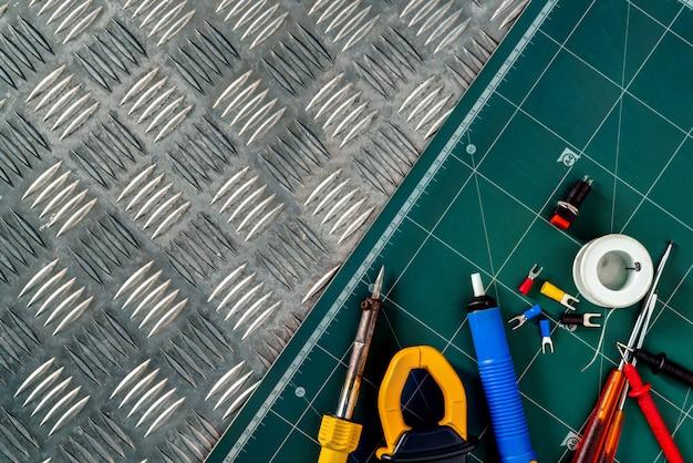 Lötwerkzeuge. lötkolben, lötdrahtspule, schraubendreher, lötfreie isolierte flachstecker auf industrieller metallprüfplatte und grüner schneidematte. Premium Fotos