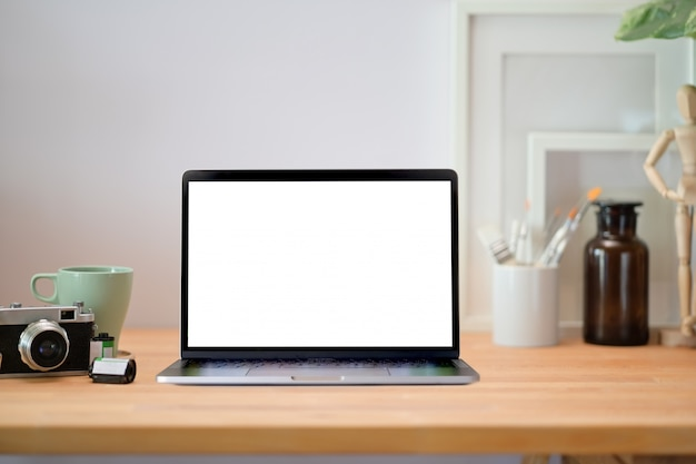Loft holz schreibtisch tisch mit laptop, poster, vintage-kamera und zubehör. Premium Fotos