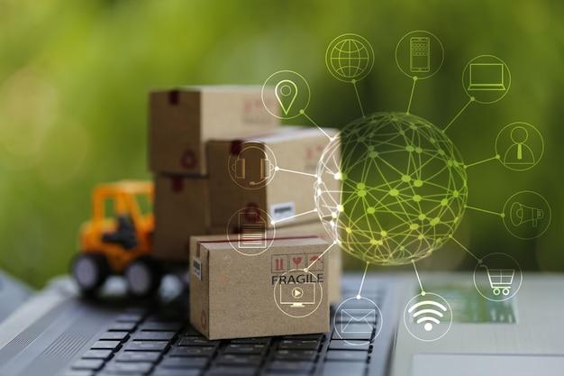 Logistik-, versorgungs- / online-einkaufskonzept: gabelstapler bewegt pappkarton auf tastatur mit symbol kundennetzwerkverbindung. internationaler fracht- oder versandservice für online-einkäufe. Premium Fotos