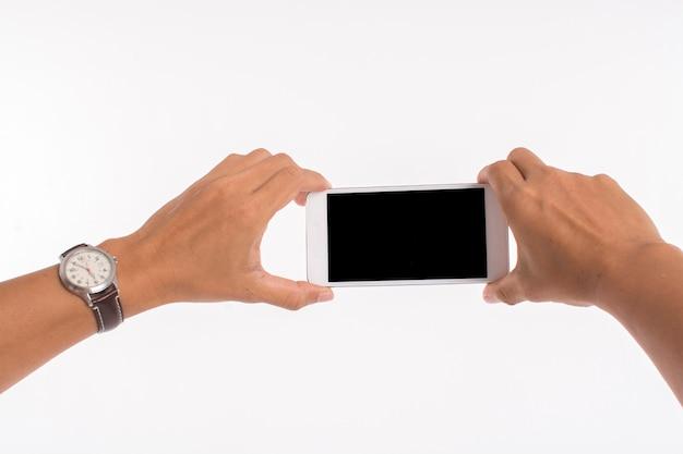 Lokalisiertes bild von den händen, die handy halten und foto auf weiß machen Premium Fotos