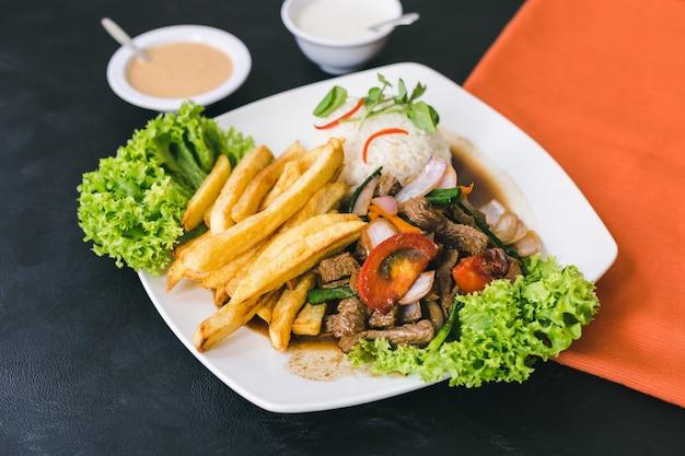 Lomo saltado mit peruanischer sauce und knoblauchsauce Premium Fotos