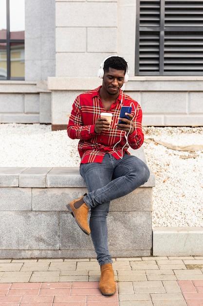 Long shot des mannes, der handy und kaffee hält Kostenlose Fotos