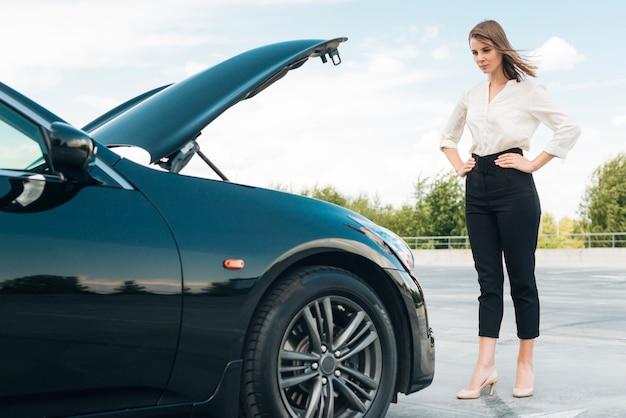 Long shot von frau und auto Kostenlose Fotos