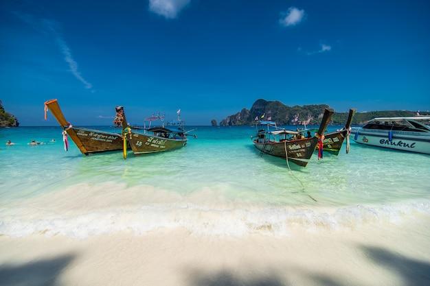 Long tail boats parken am weiß und strand auf phi phi island in thailand Kostenlose Fotos