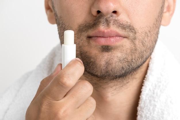 Lose-up von mann mit handtuch um den hals hält lippenbalsam Kostenlose Fotos