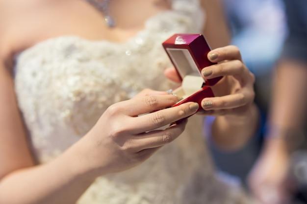 Loseup foto einer braut, die einen kasten mit goldringen anhält Premium Fotos