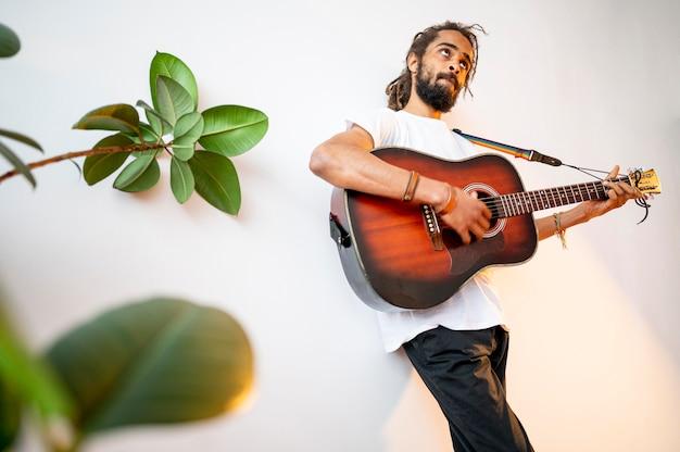 Low angle man spielt gitarre mit kopierraum Kostenlose Fotos