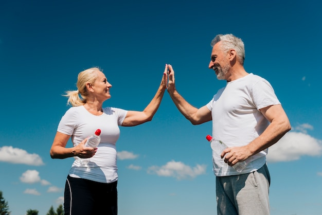 Low angle old people high fiving Kostenlose Fotos