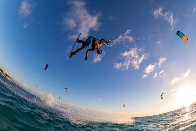 Low angle shot einer person, die gleichzeitig beim kitesurfen surft und einen fallschirm fliegt Kostenlose Fotos