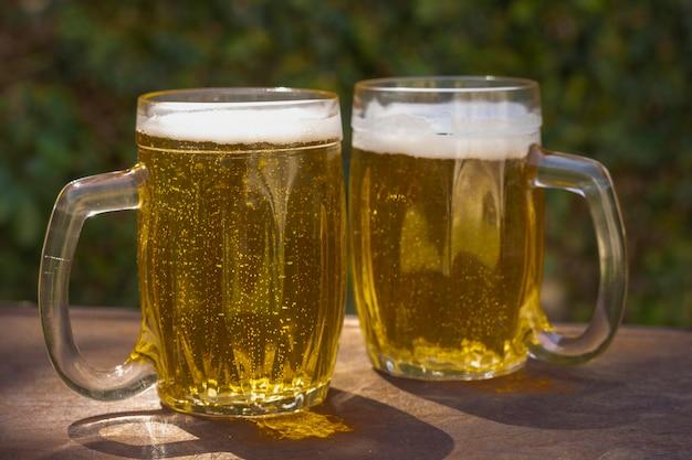 Low angle zwei pints mit frischem bier Kostenlose Fotos