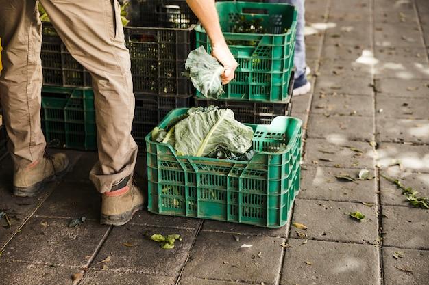 Lowsection von füllenden kisten des verkäufers mit frischgemüse am supermarkt Kostenlose Fotos