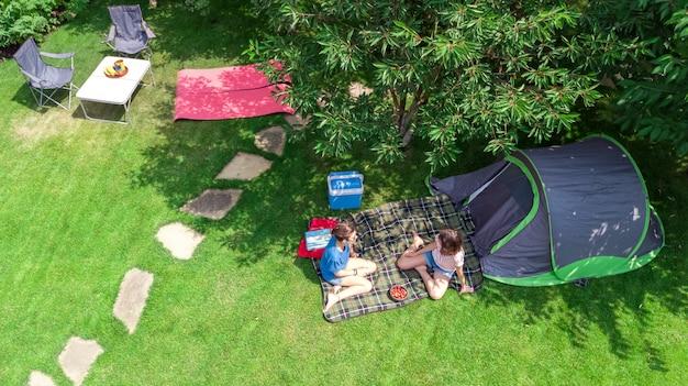 Luft draufsicht des campingplatzes von oben, mutter und tochter, die spaß, zelt und campingausrüstung unter baum, familienurlaub im camp im freienkonzept haben Premium Fotos