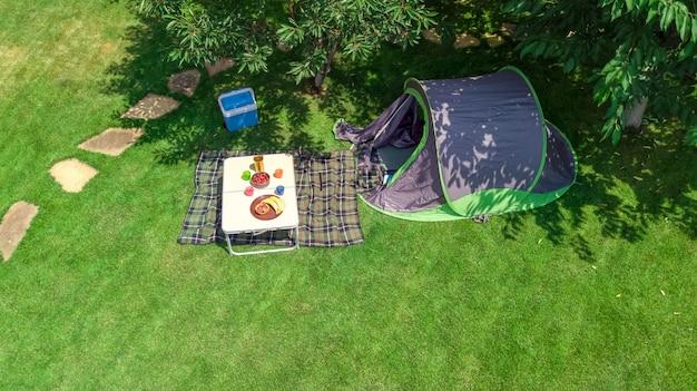 Luftansicht des campingplatzes von oben, zelt- und campingausrüstung unter baum, familienurlaub im camp im freien konzept Premium Fotos