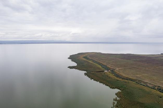 Luftaufnahme am riesigen see mit einem grünen sre und frühem abendhimmel Kostenlose Fotos