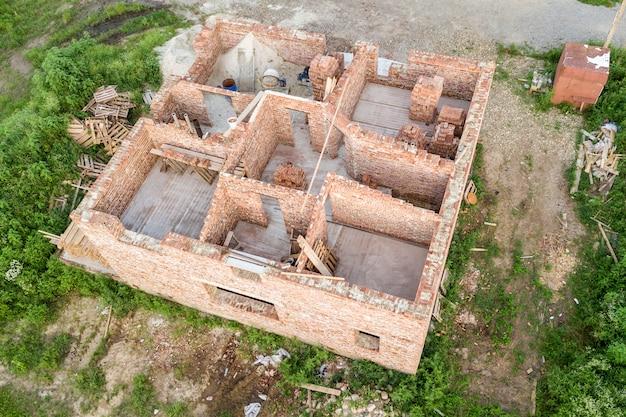 Luftaufnahme der baustelle für zukünftiges haus, ziegelsteinkellerfußboden und stapel ziegelstein für bau. Premium Fotos