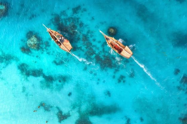 Luftaufnahme der fischerboote im klaren blauen wasser bei sonnenuntergang im sommer Premium Fotos