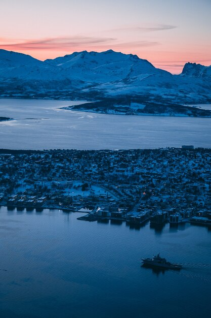 Luftaufnahme der gebäude und der schneebedeckten berge in tromsø, norwegen Kostenlose Fotos