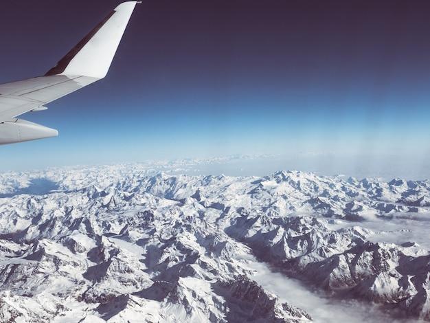 Luftaufnahme der italienischen schweizer alpen im winter, mit generischem flugzeugflügel. schneebedeckte bergkette und gletscher. weitblick, klarer blauer himmel. Premium Fotos