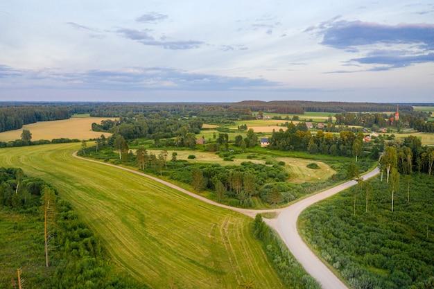 Luftaufnahme der ländlichen landschaft lettlands mit landwirtschaftlichen feldern, wäldern und straßen bei sonnenuntergang Premium Fotos