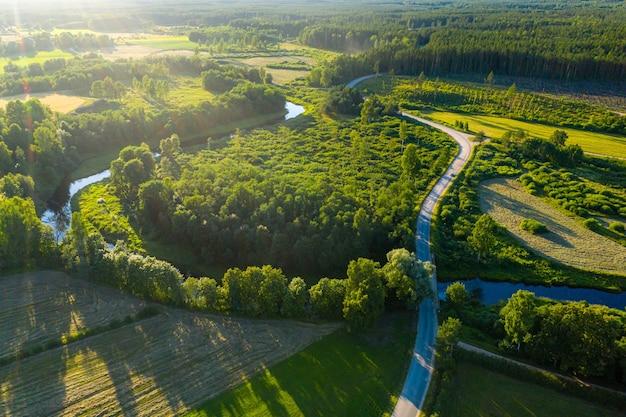 Luftaufnahme der lettischen ländlichen landschaft mit einem gewundenen fluss, wäldern und landstraßen bei sonnenuntergang Premium Fotos