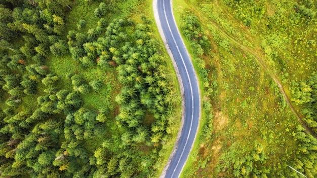 Luftaufnahme der verdrehung der straße unter dem wald und den bäumen. sonnenuntergangfeld in litauen. Premium Fotos