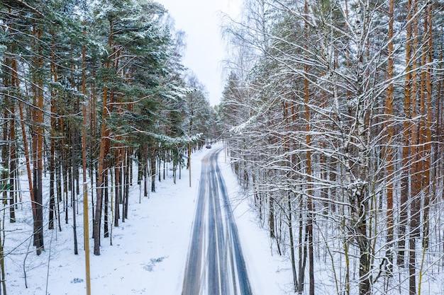 Luftaufnahme der winterstraße durch den wald Kostenlose Fotos