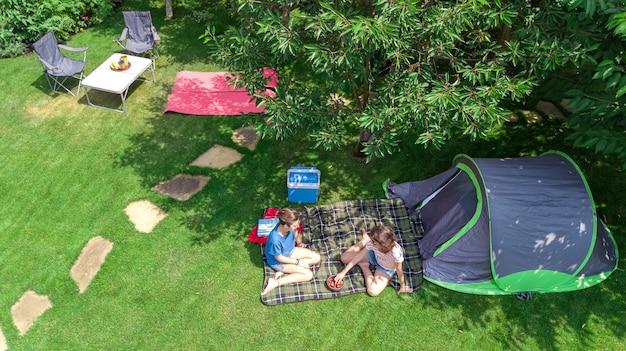Luftaufnahme des campingplatzes von oben, mutter und tochter, die spaß, zelt und campingausrüstung unter baum haben, familienurlaub im camp im freien konzept Premium Fotos