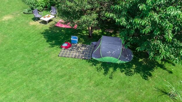 Luftaufnahme des campingplatzes von oben, zelt und campingausrüstung unter baum Premium Fotos