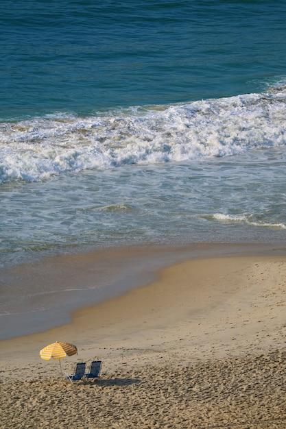 Luftaufnahme des copacabana-strandes mit einem paar strandstühlen und sonnenschirm Premium Fotos