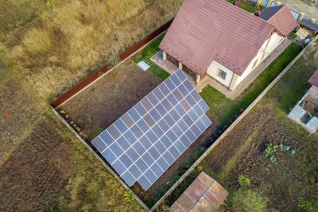 Luftaufnahme des großen blauen solarpanels, das auf grundstruktur nahe privatem haus installiert wird. Premium Fotos