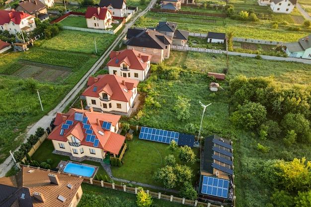Luftaufnahme des ländlichen wohngebiets mit privathäusern zwischen grünen feldern bei sonnenaufgang. Premium Fotos