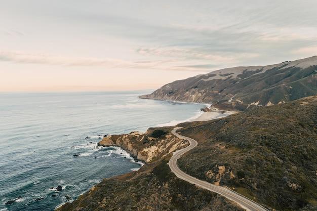Luftaufnahme des ozeans an einer im grünen bedeckten felsformation Kostenlose Fotos