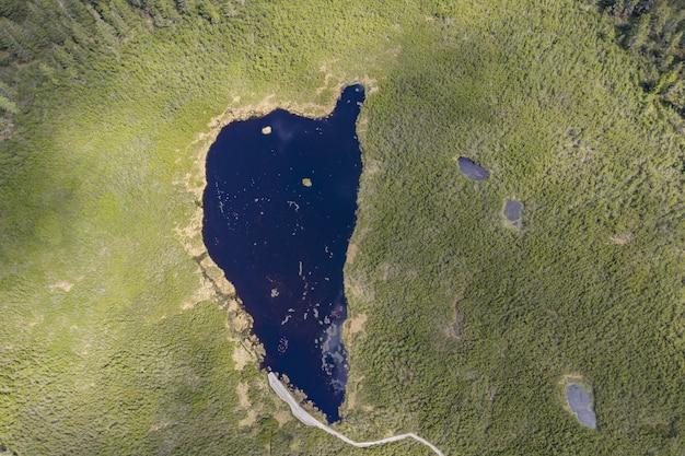 Luftaufnahme des ribnica-sees, umgeben von einem feld in slowenien Kostenlose Fotos