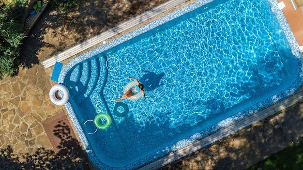 Luftaufnahme des schönen mädchens im schwimmbad von oben schwimmen auf aufblasbarem ringkrapfen und hat spaß im wasser im familienurlaub auf tropischem ferienort Premium Fotos